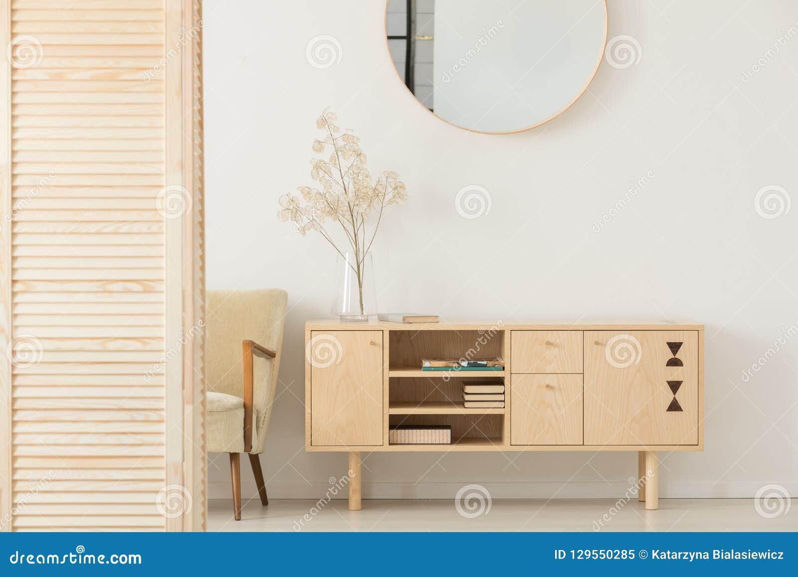在白色墙壁上的圆的镜子在简单的前室的木内阁上内部与扶手椅子