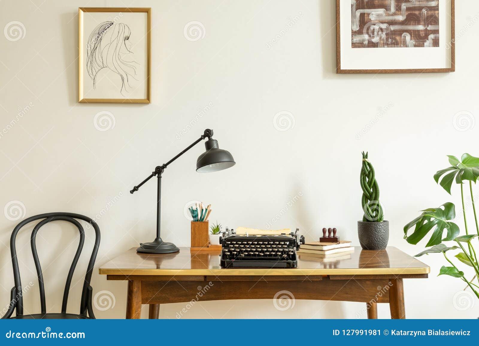 在白色墙壁上的被构筑的图画在古董上,有葡萄酒的木书桌,在家庭办公室内部的黑打字机