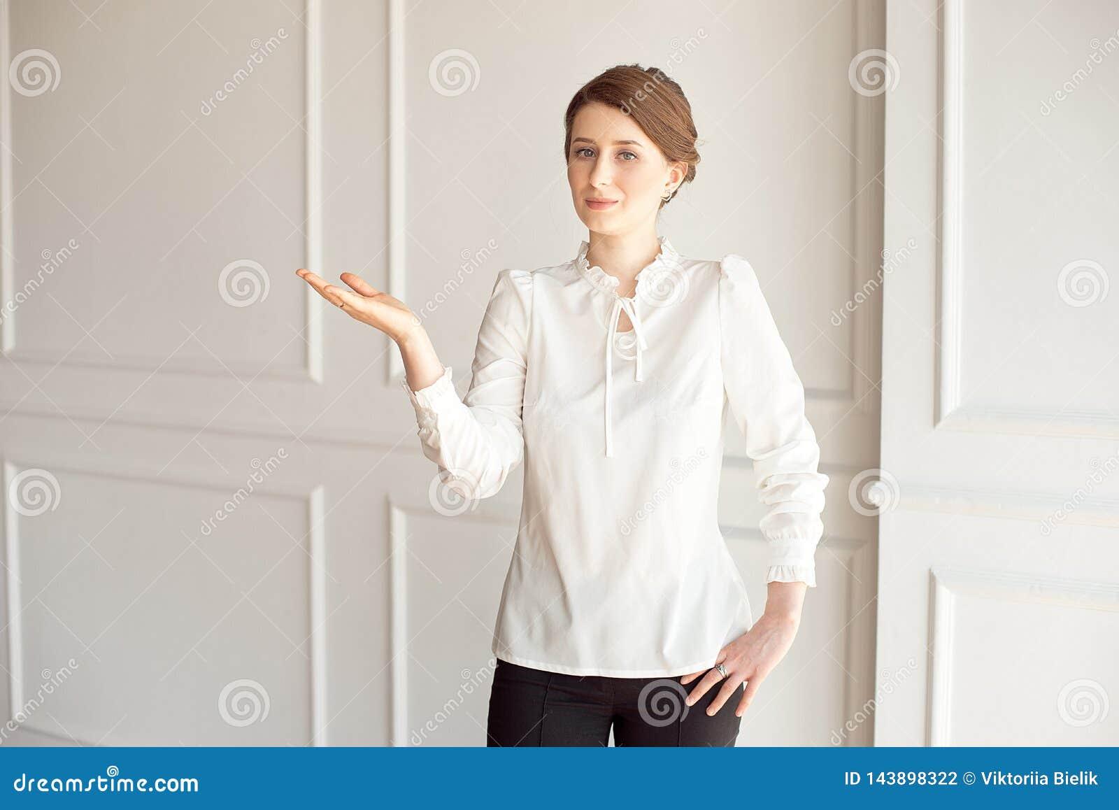 在白色墙壁附近的愉快的年轻女人身分 显示指向的手copyspace一个地方