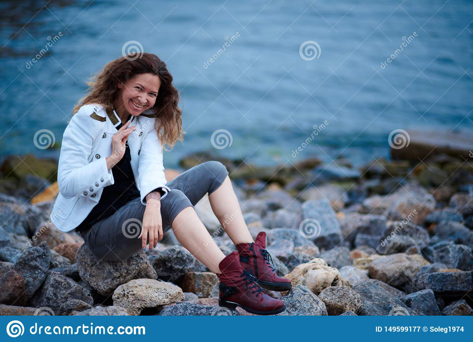 在白色夹克和宽长裤打扮的时兴的女孩摆在海附近在晚上