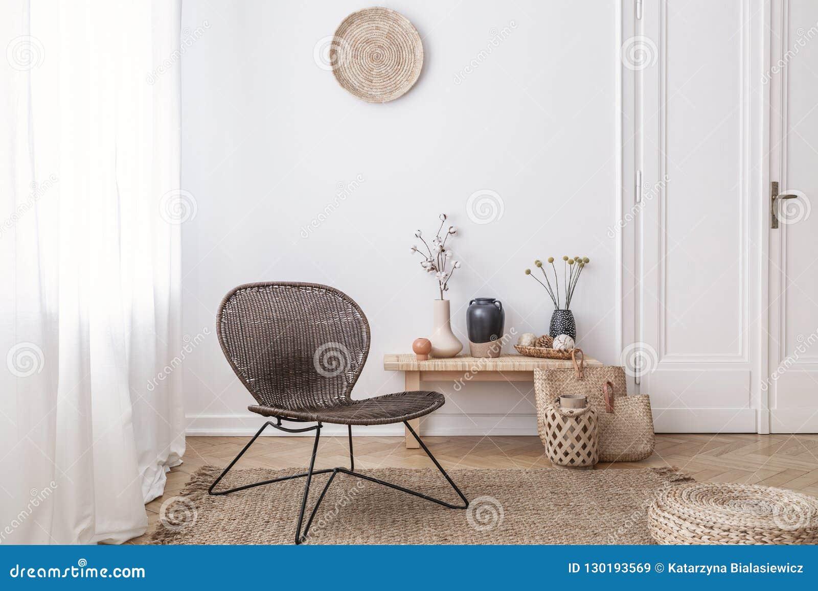 在白色客厅内部的黑暗,现代由天然材料做的藤椅与一个长木凳和装饰