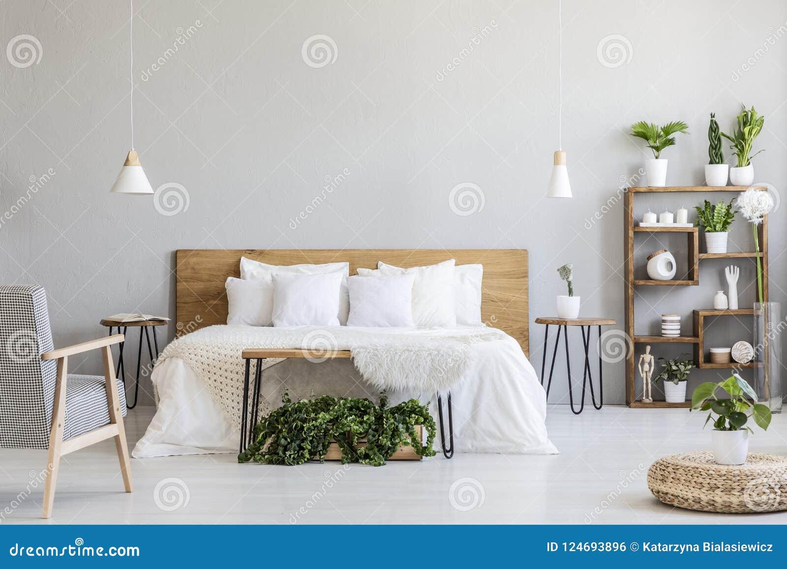 在白色木床附近的被仿造的扶手椅子在与蒲团和植物的灰色卧室内部 实际照片