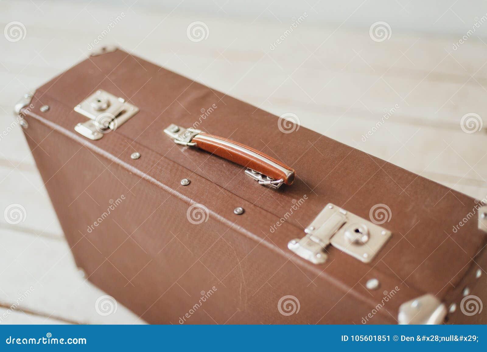 在白色木板走道地板上的老棕色手提箱