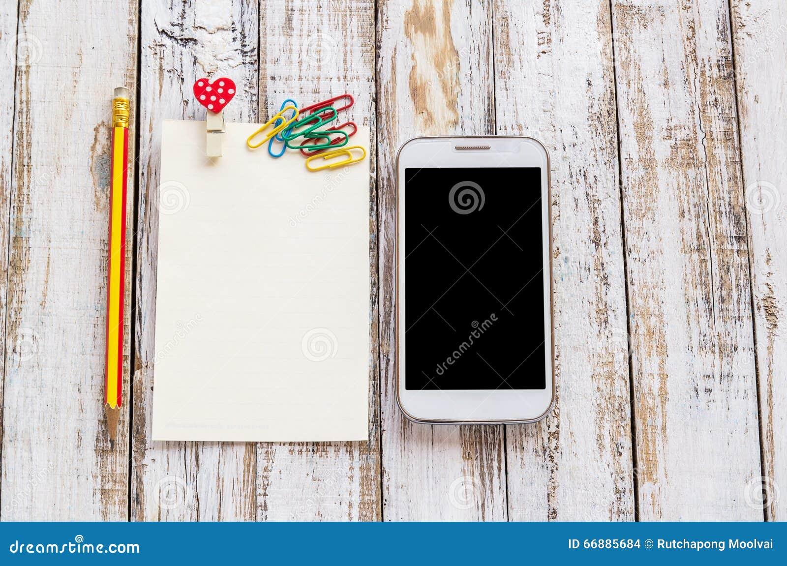 在白色木桌上的纸和巧妙的电话