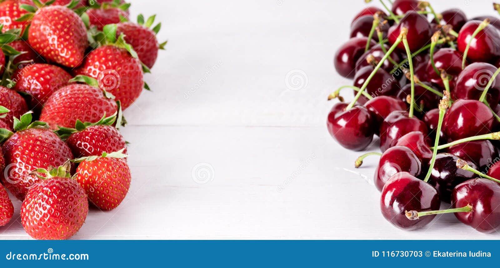 在白色木长期背景甜草莓和樱桃框架的新鲜的美丽的成熟莓果