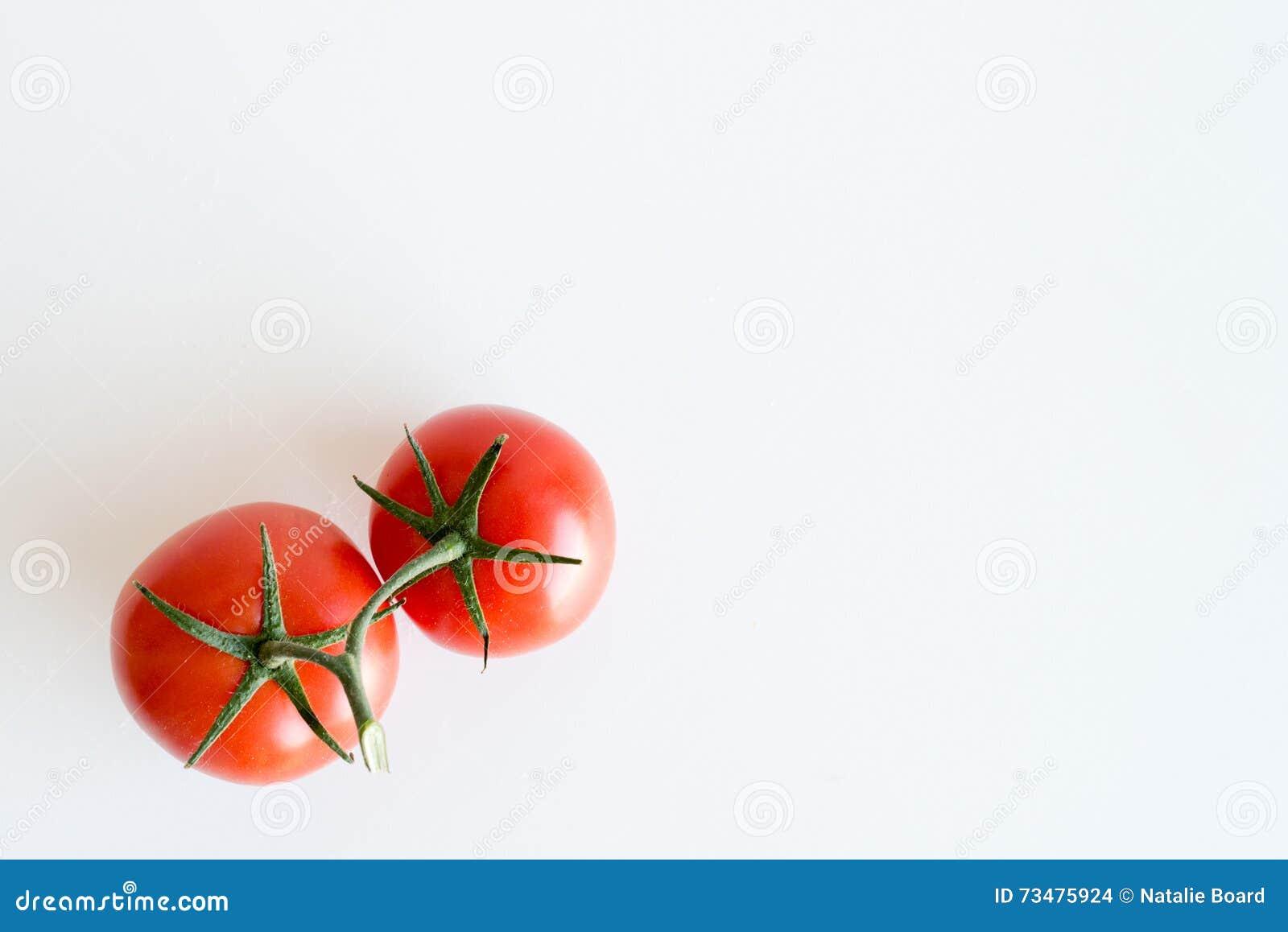 在白色桌上的两个红色蕃茄从上面
