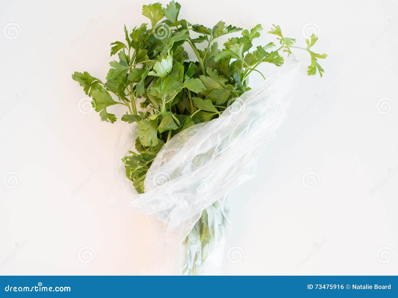 在白色桌上的平的叶子荷兰芹从上面