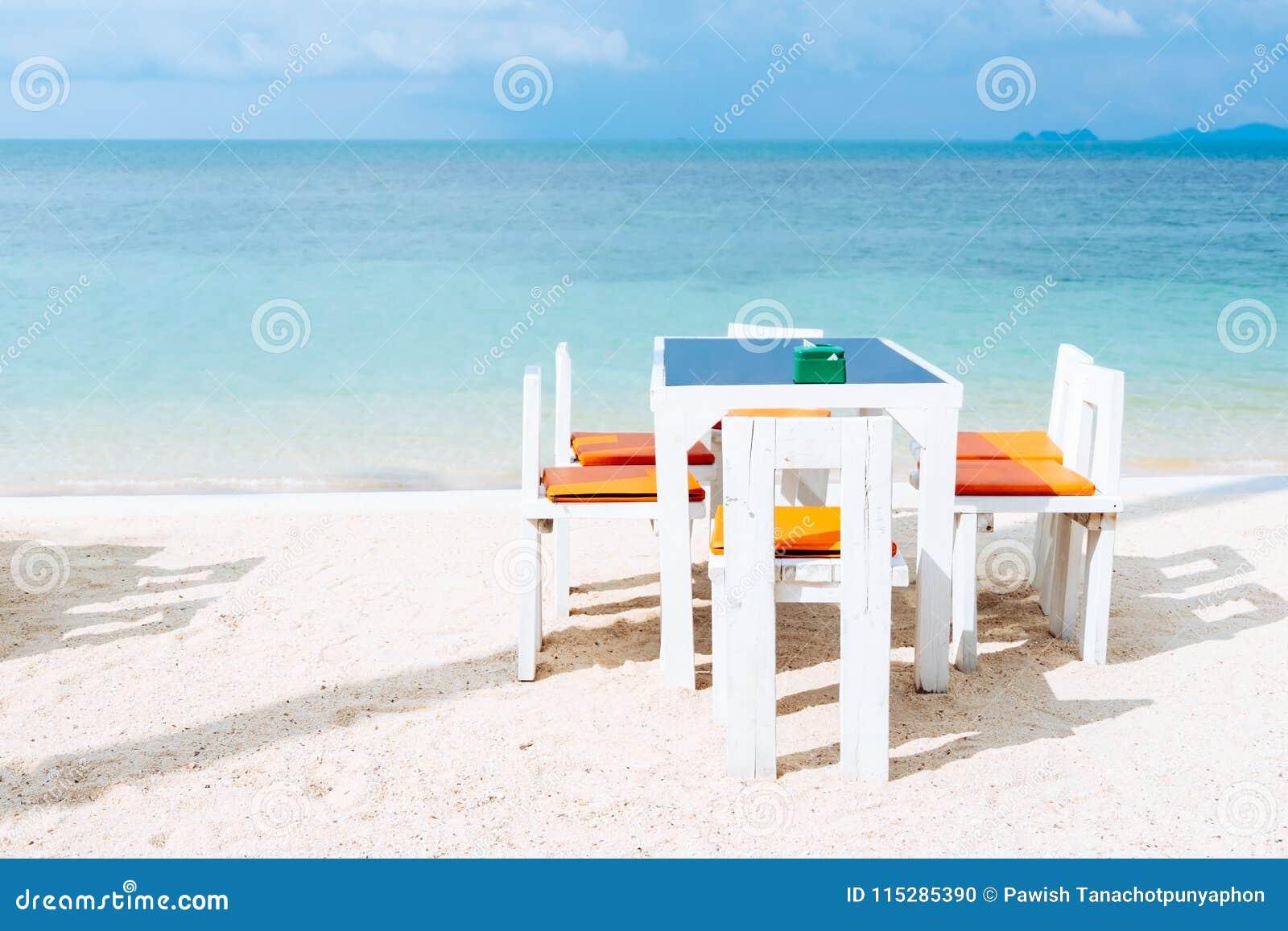 在白色沙子夏天的海滩的室外白色饭桌设置