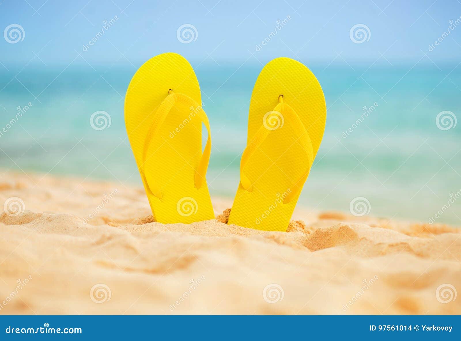 在白色沙子海滩的黄色凉鞋触发器有蓝色海和天空背景在暑假复制空间