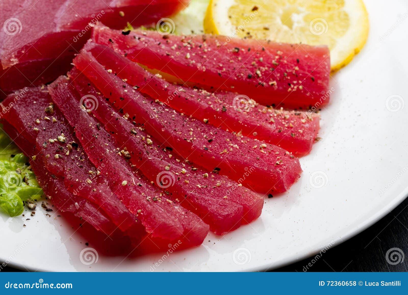 在白色盘的未加工的金枪鱼生鱼片在木backgr