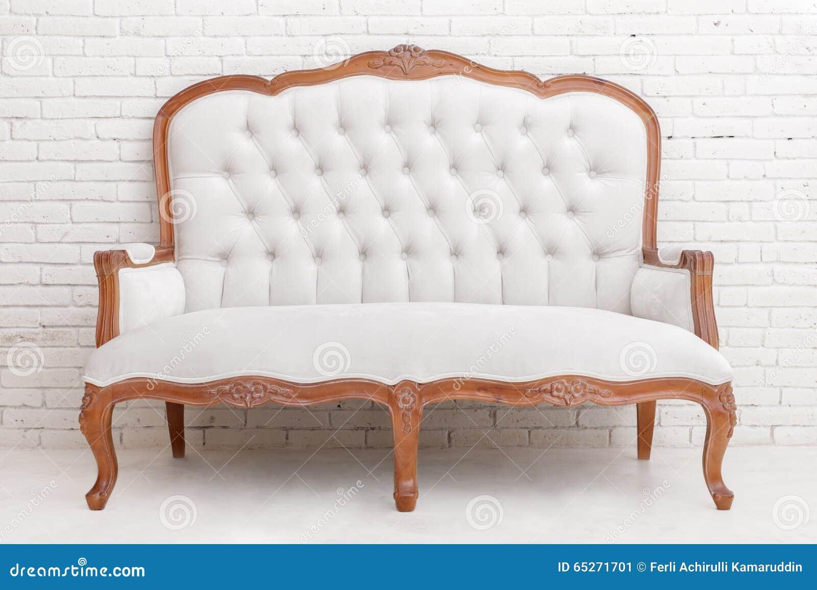 白色古典样式沙发充分的画象在白色砖墙上的.图片