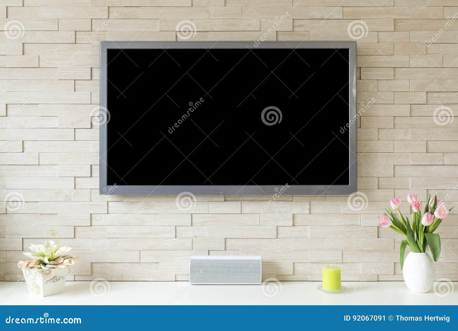 在白色砖墙的空白的现代平面屏幕电视有拷贝空间的