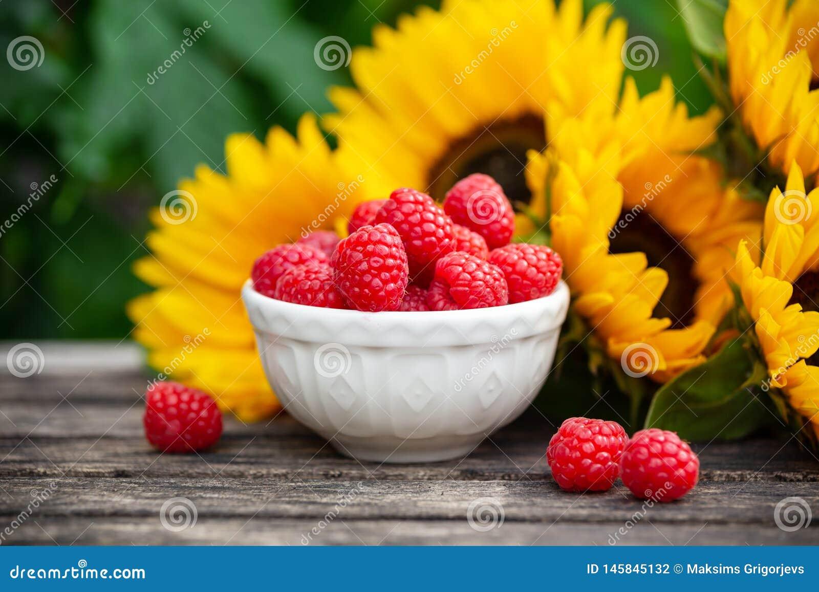 在白色碗的成熟莓有在木桌,夏天题材上的向日葵花束的