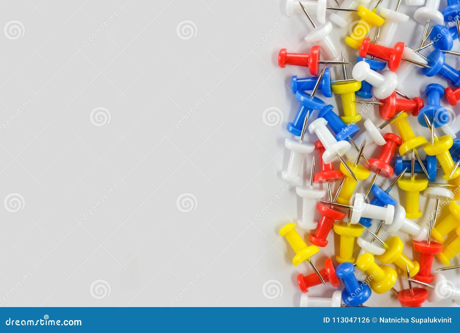 在白色背景右侧,上色推挤别针红色,黄色,白色和蓝色小组