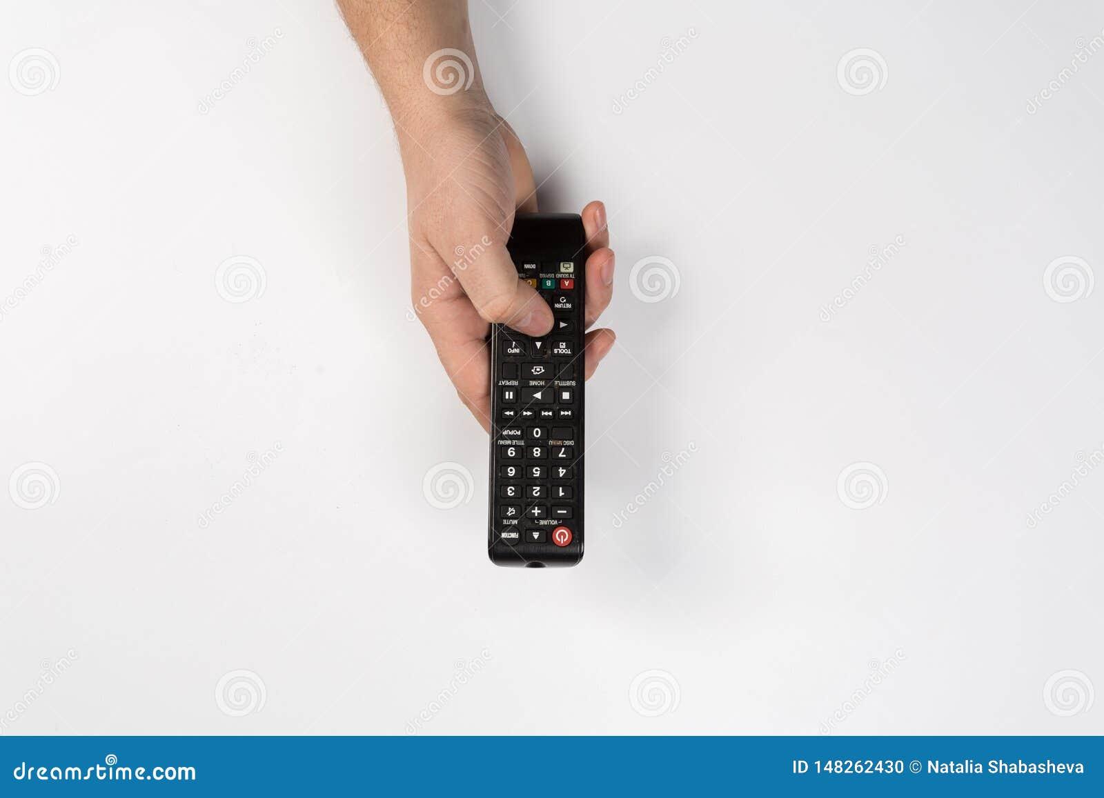 在白色背景有电视遥控的手隔绝的