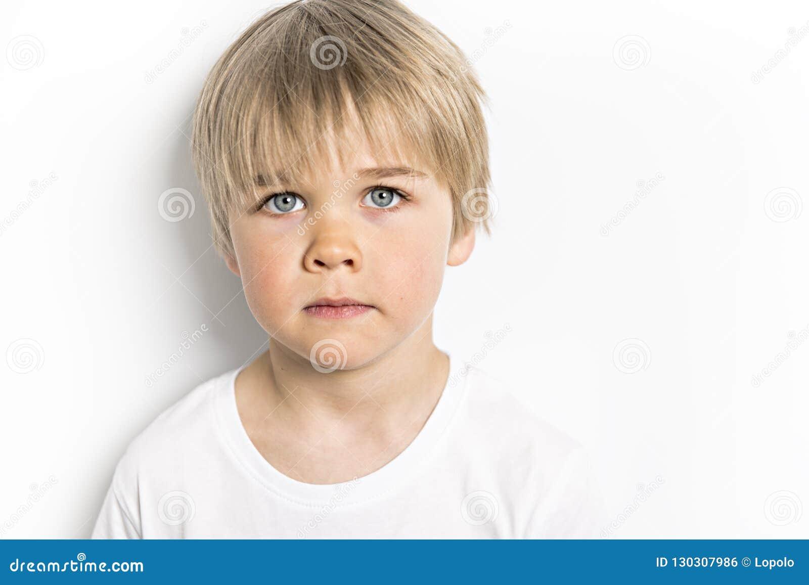 在白色背景的一张逗人喜爱的五岁的男孩演播室画象