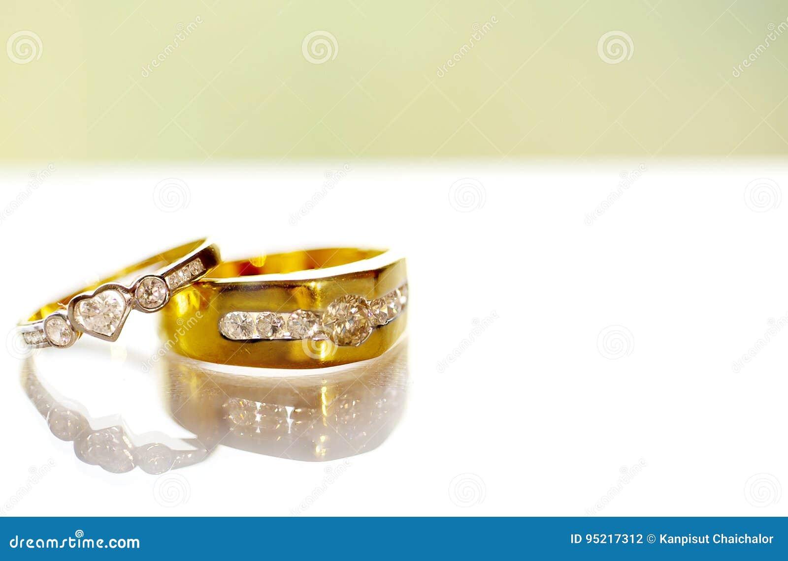 在白色背景的两个金钻石婚圆环 与金刚石的金婚圆环在白色背景