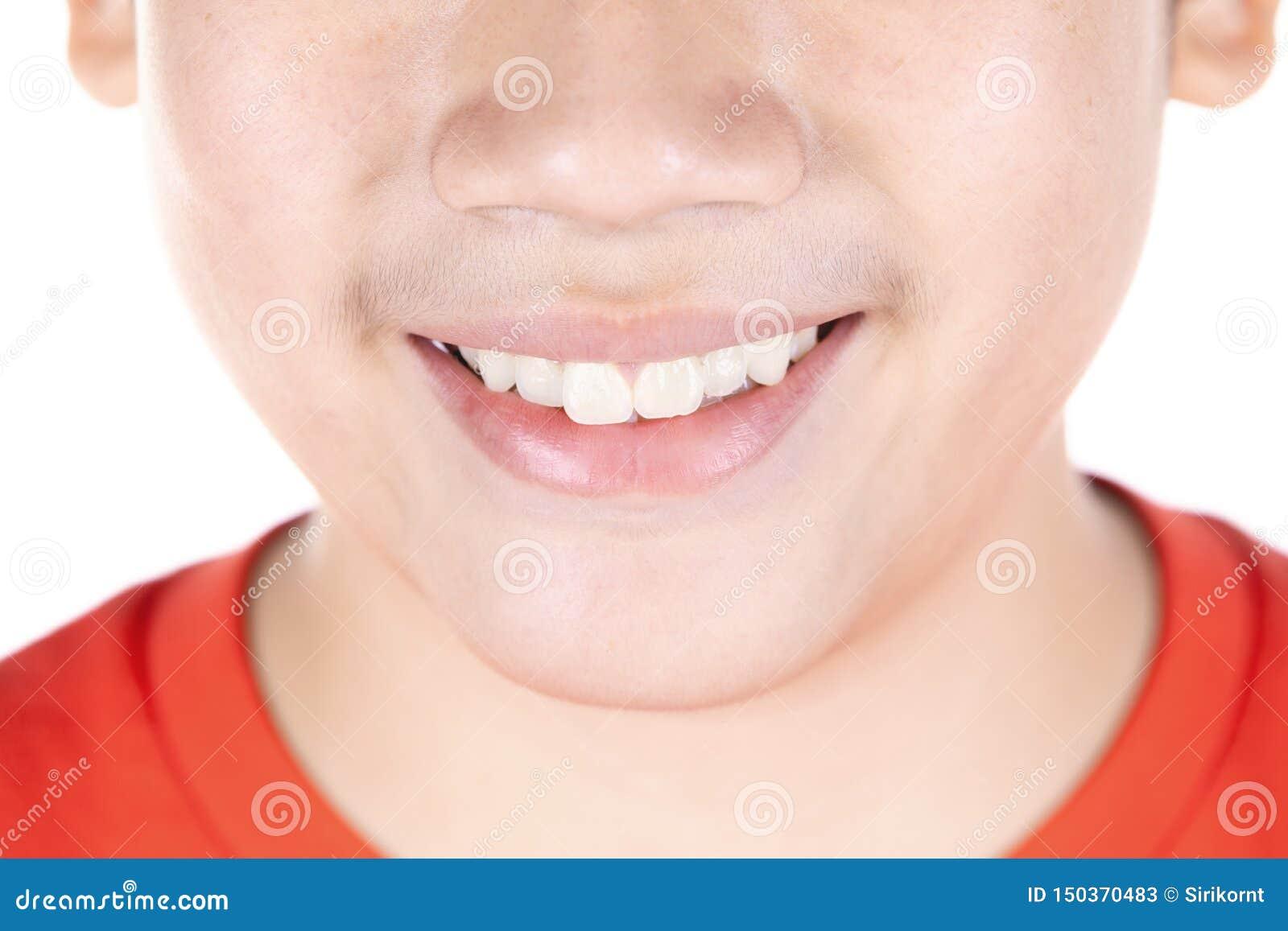 在白色背景隔绝的亚裔男孩接近的嘴