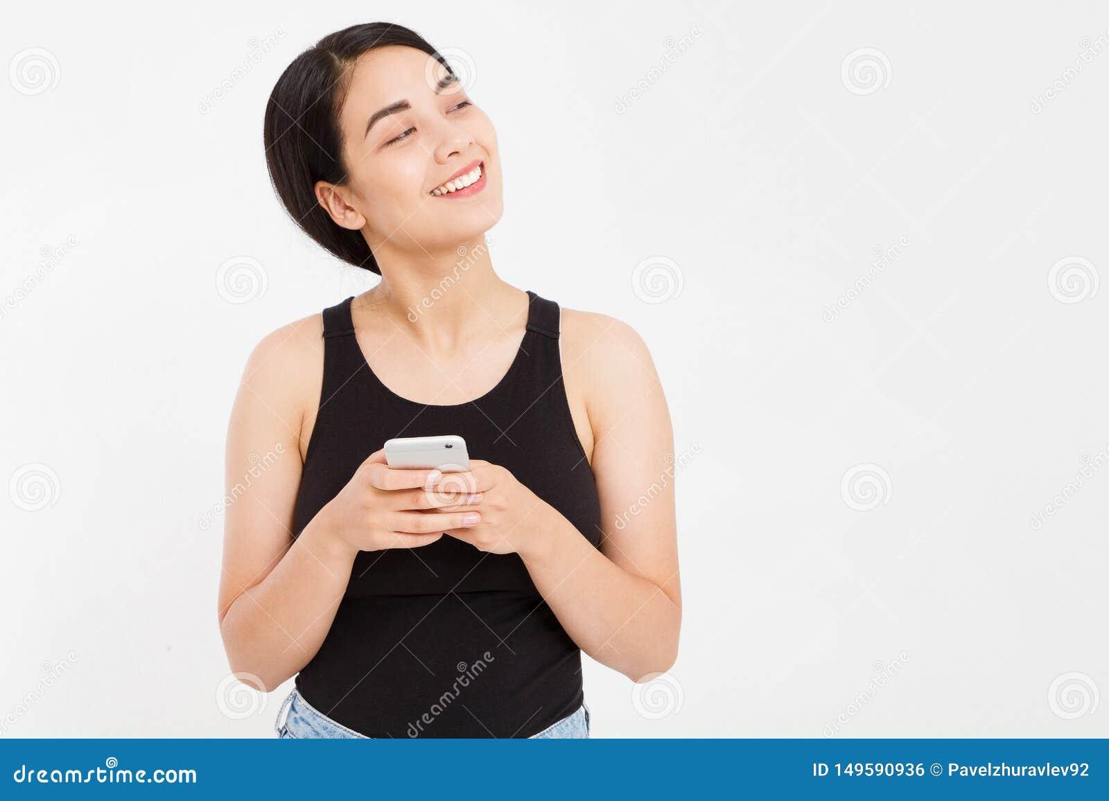 在白色背景隔绝的逗人喜爱的愉快的亚洲女孩举行电话