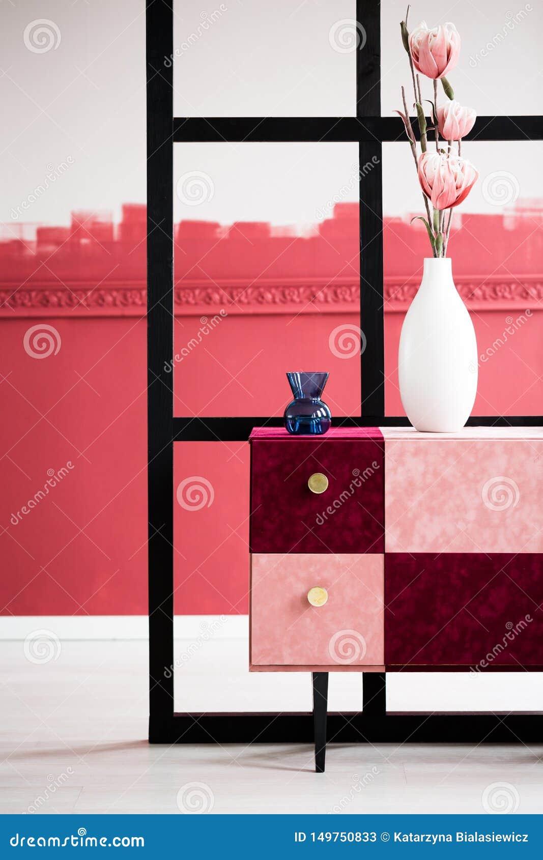 在白色花瓶的桃红色花在手工制造桃红色和伯根地洗脸台的蓝色花瓶旁边