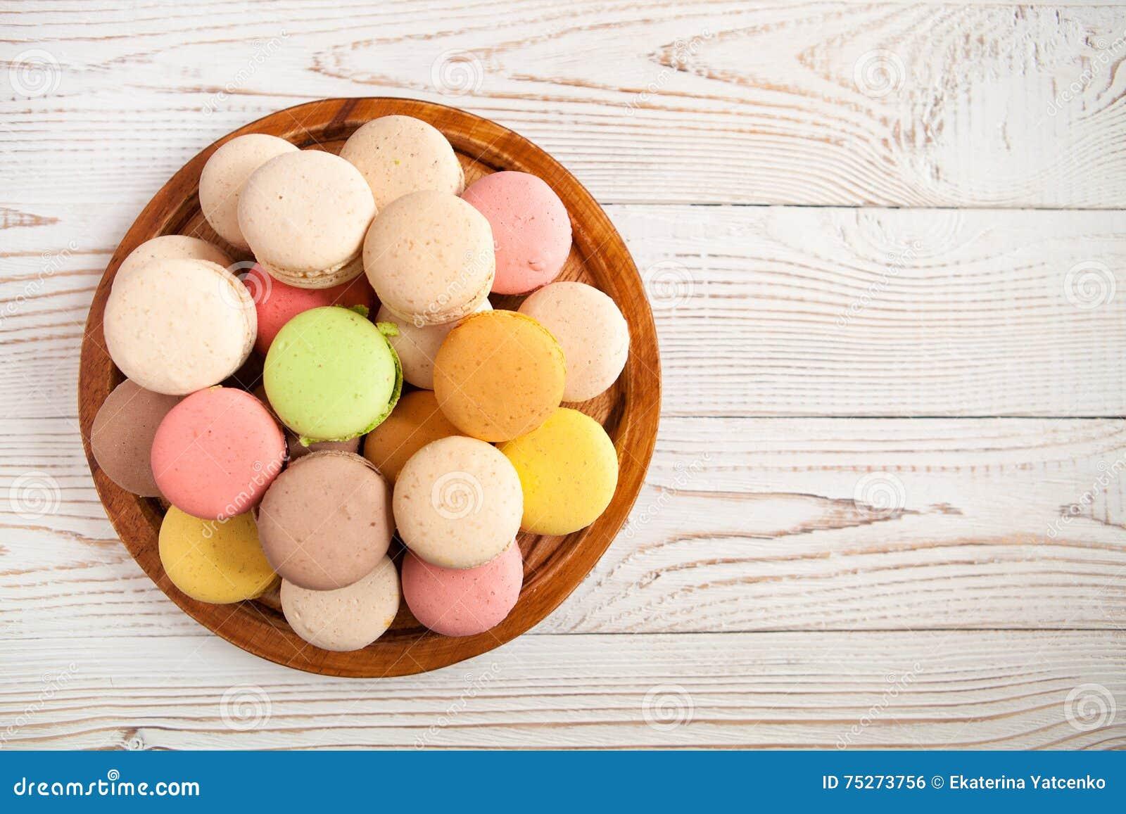 在白色葡萄酒桌上的五颜六色的蛋白杏仁饼干,与拷贝空间