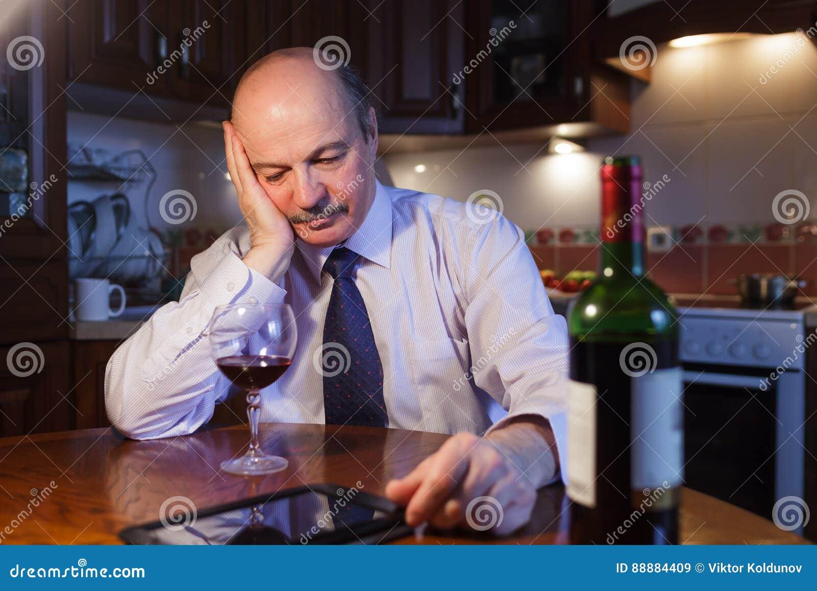 在白色衬衣和领带的疲乏的商人喝红葡萄酒