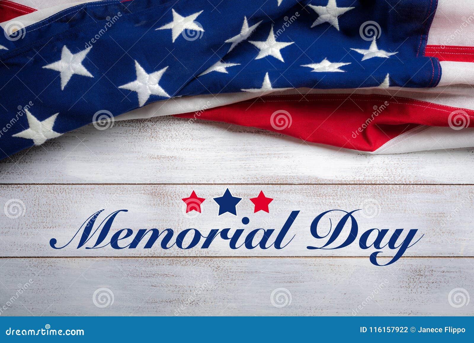 在白色被佩带的木背景的美国国旗与阵亡将士纪念日问候