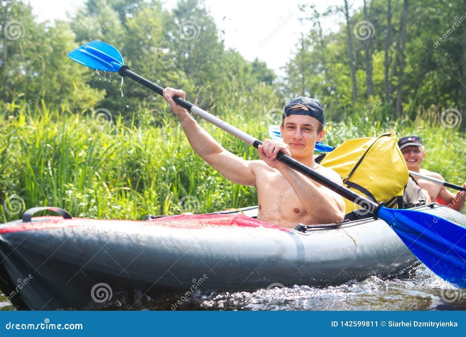 在皮船的划船周末 用浆划在河漂流期间的愉快的人 划皮船的