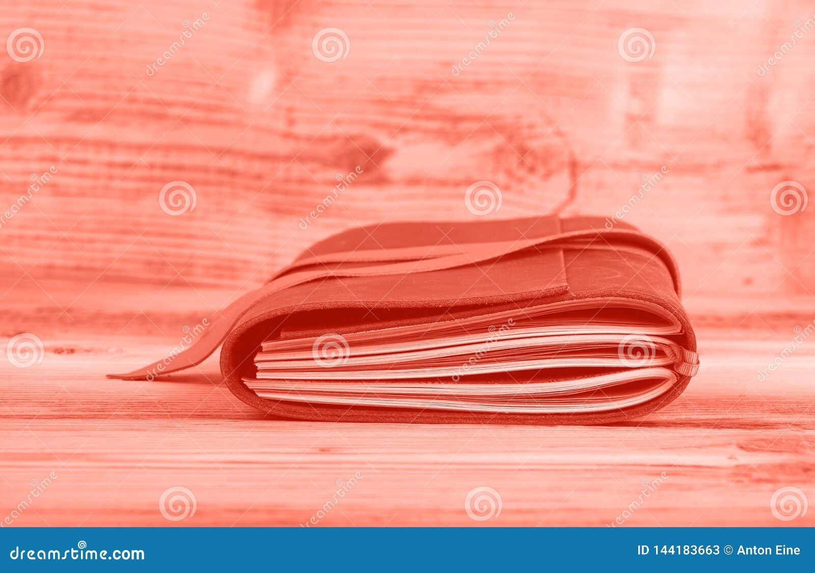 在皮革盖子的桃红色被定调子的笔记本在桌上