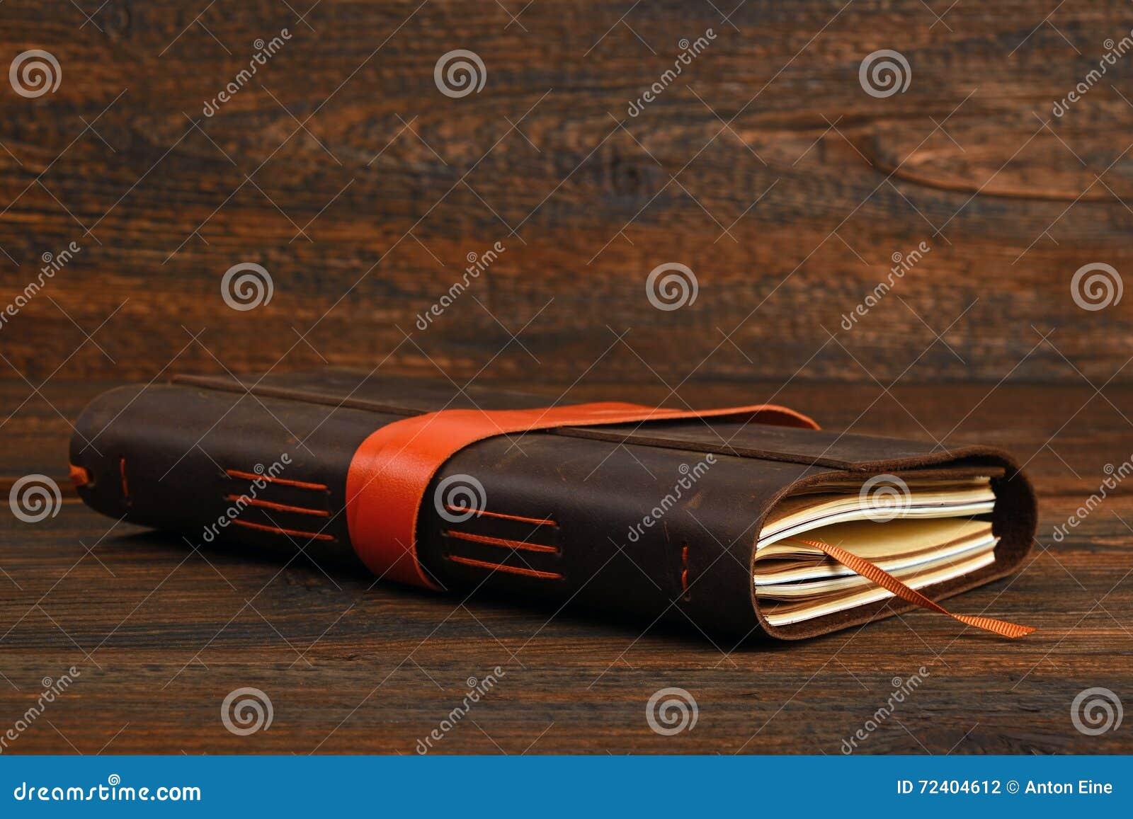 在皮革盖子的笔记本在木桌上