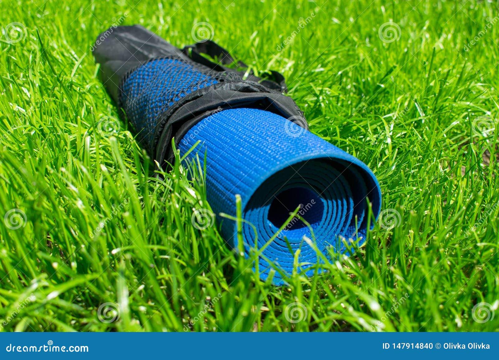 在盖子在绿草,训练的概念和休闲的瑜伽席子