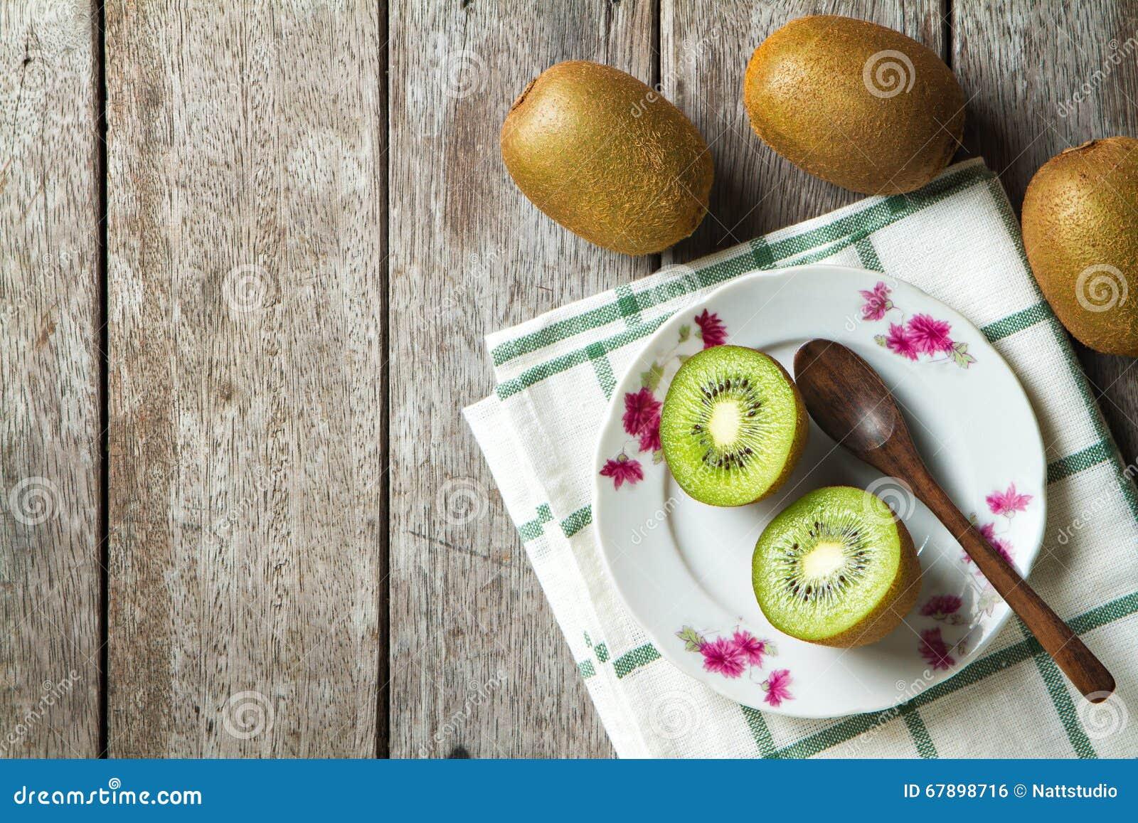 在盘的在木背景的猕猴桃和匙子