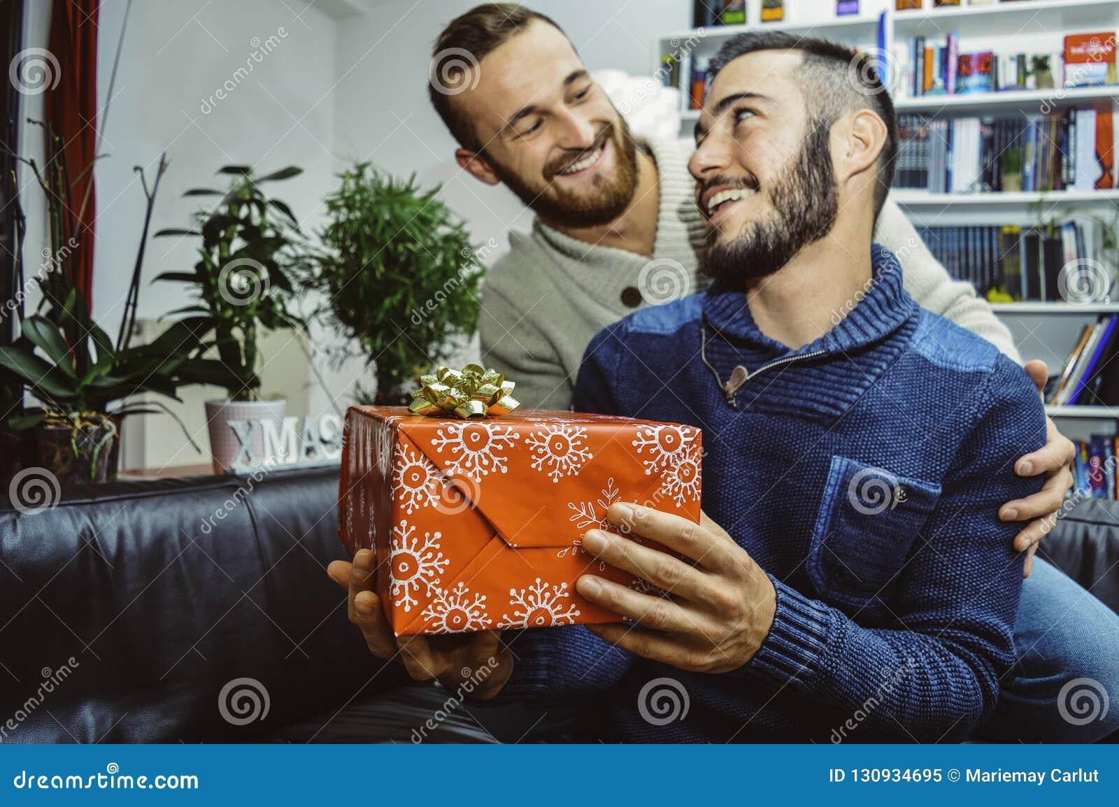 在看彼此的爱的愉快的微笑的年轻英俊的快乐夫妇庆祝和给礼物