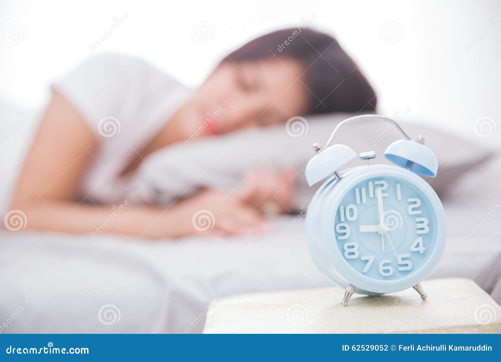 在睡觉在床上的前面妇女的闹钟