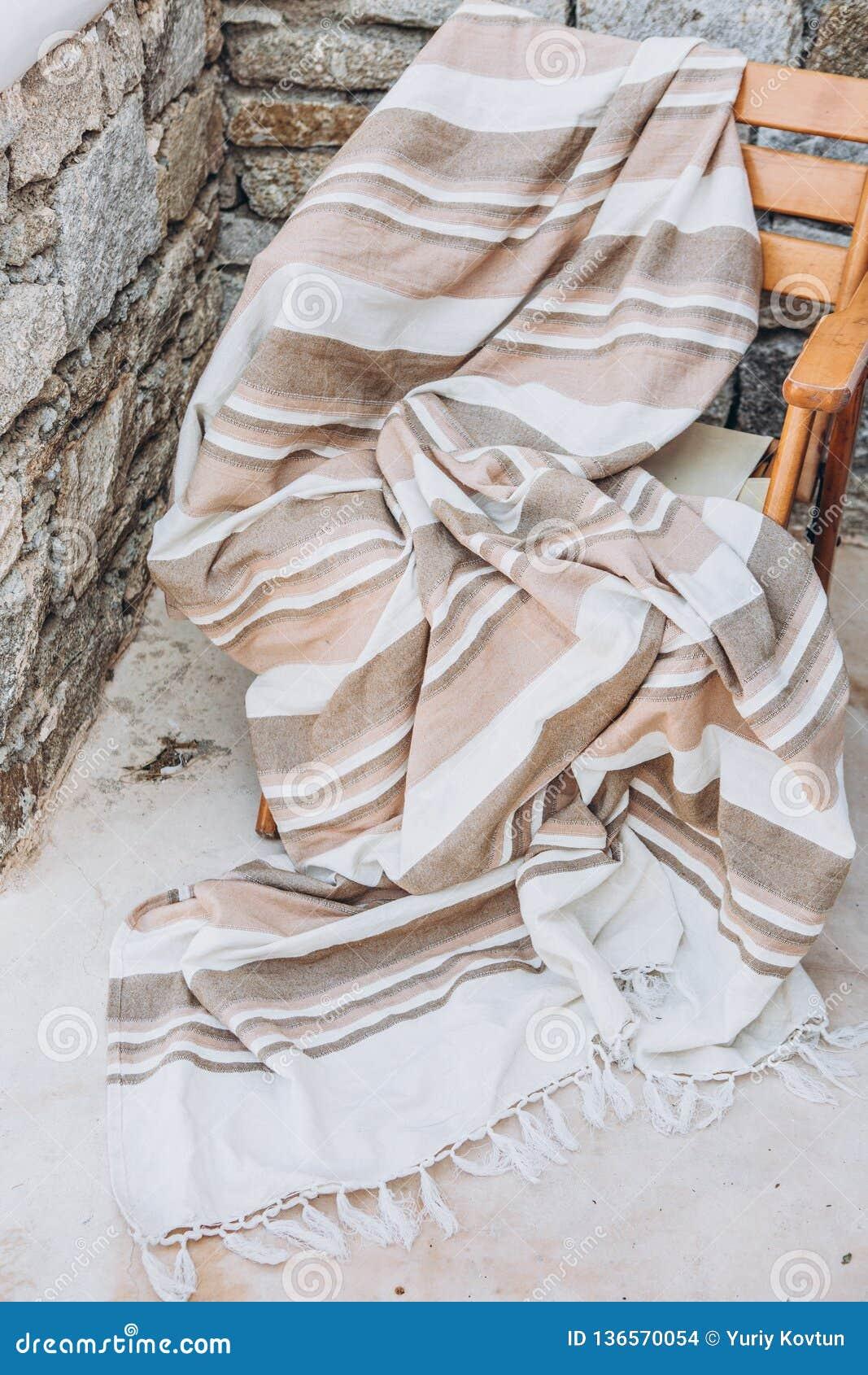 在石墙纹理之外的格子花呢披肩米黄椅子