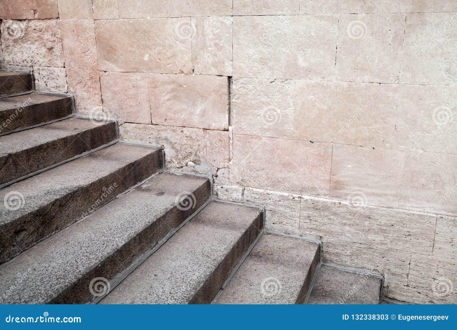 在石墙附近的空的老具体楼梯