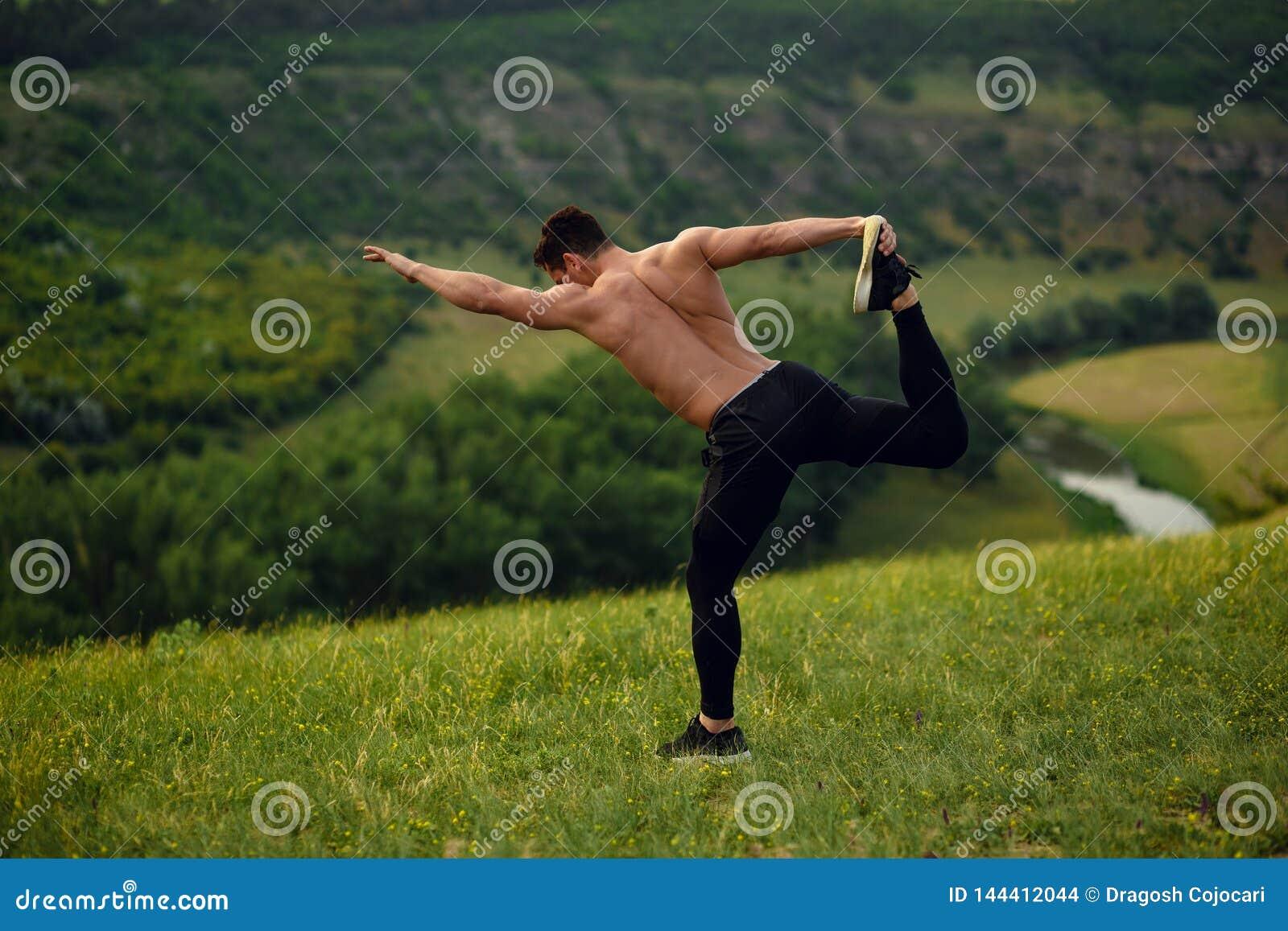 在石头,有赤裸躯干的运动员年轻人的顶视图在做伸展运动,风景背景的运动服
