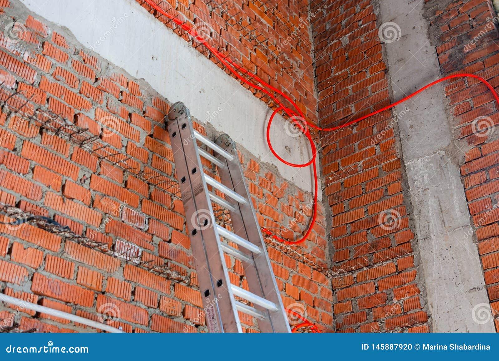 在砖墙和导线的快速的梯子