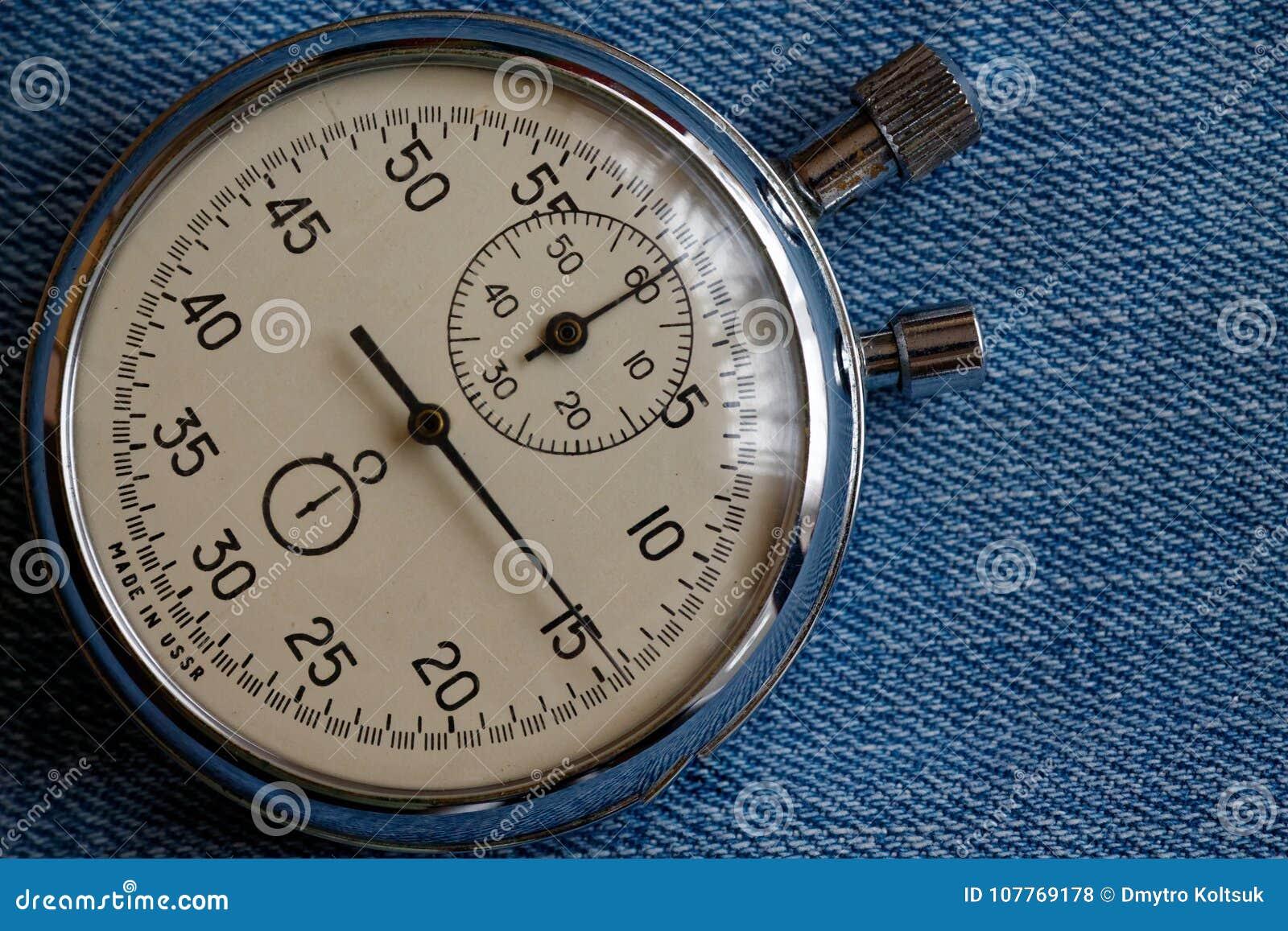 在破旧的蓝色牛仔裤背景,价值措施时间、老时钟箭头分钟和第二个准确性定时器纪录的秒表