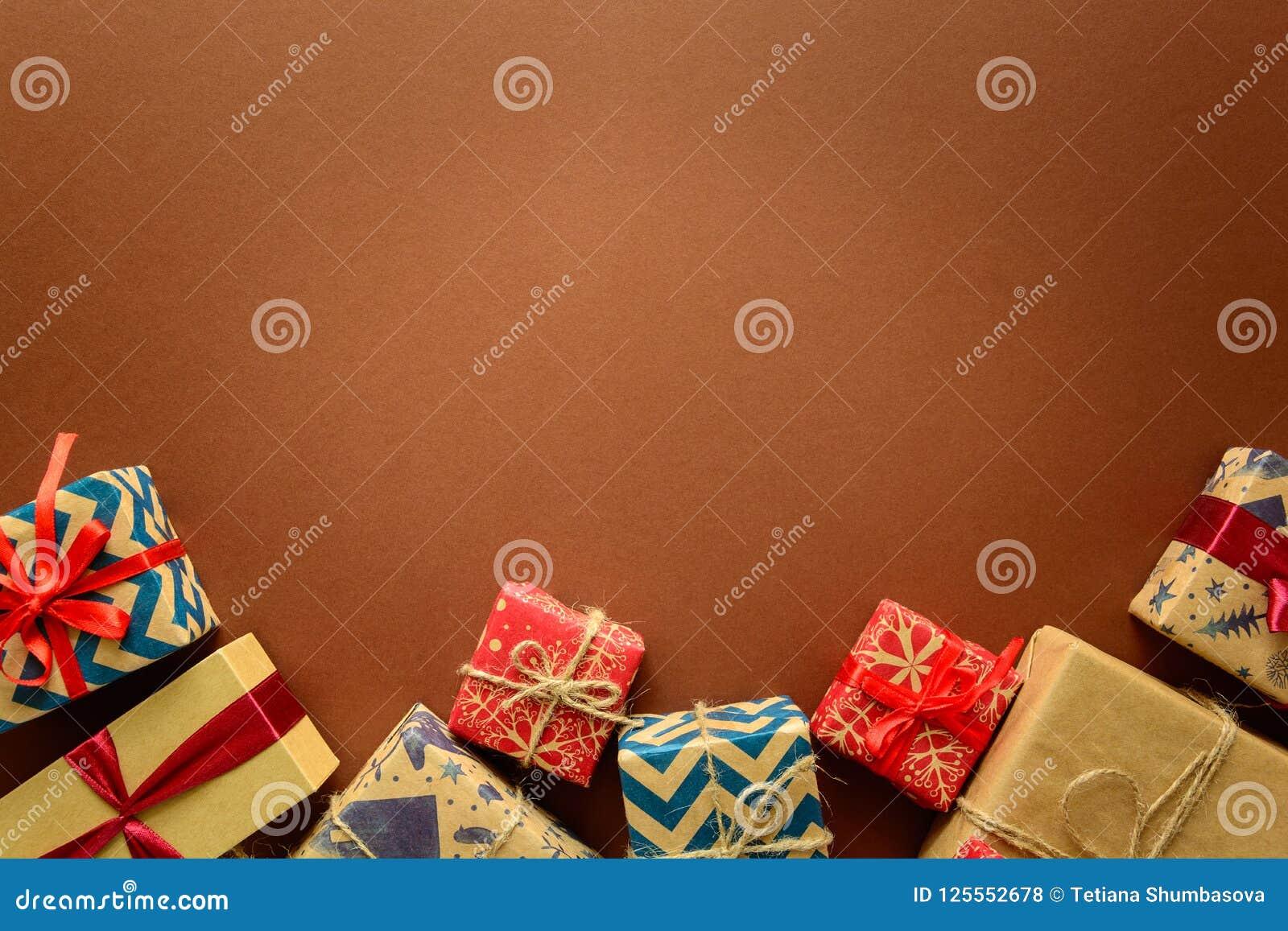在礼物纸包裹的圣诞节礼物的顶视图装饰用在包装纸背景的丝带