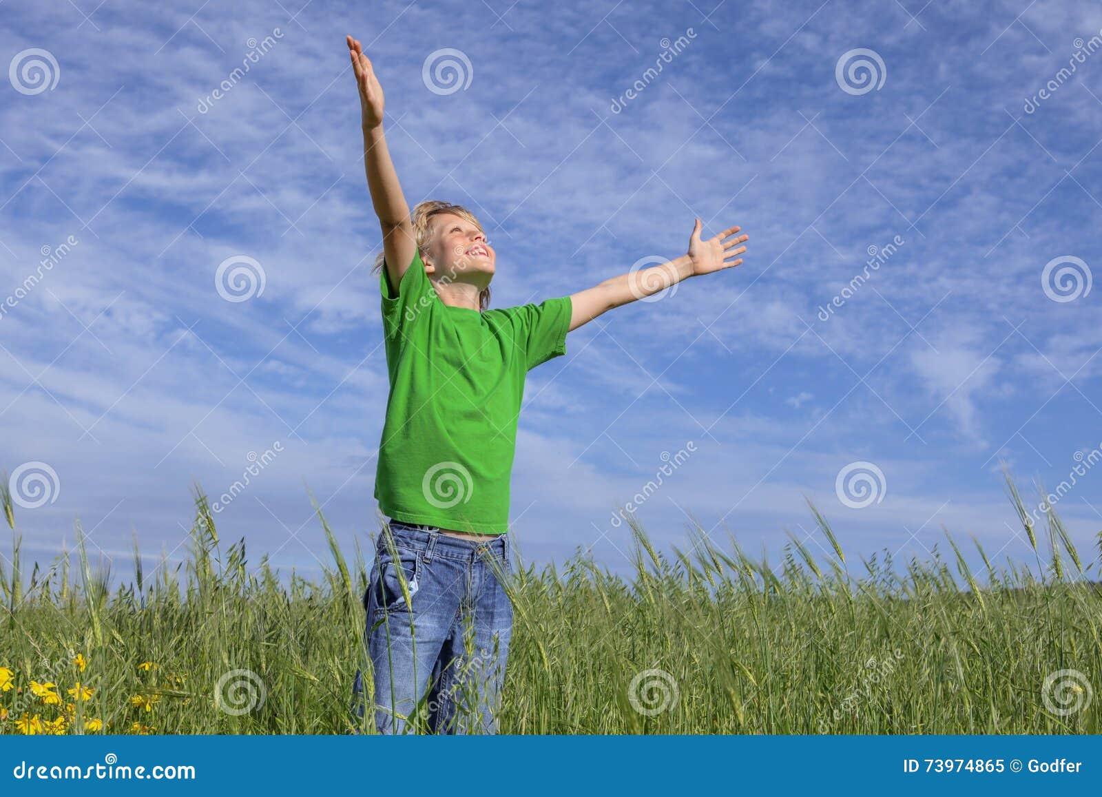 在祷告举的愉快的基督徒男孩胳膊