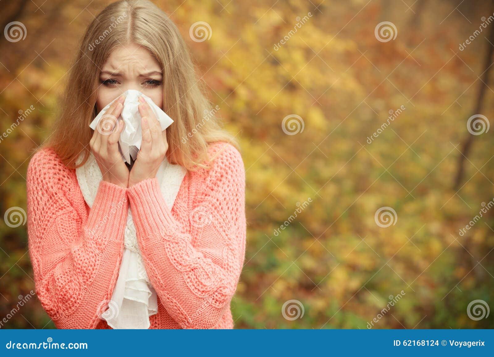 在秋天公园打喷嚏在组织的病的不适的妇女