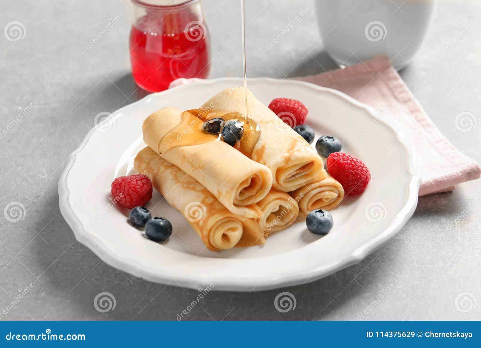 在稀薄的薄煎饼的倾吐的蜂蜜用莓果
