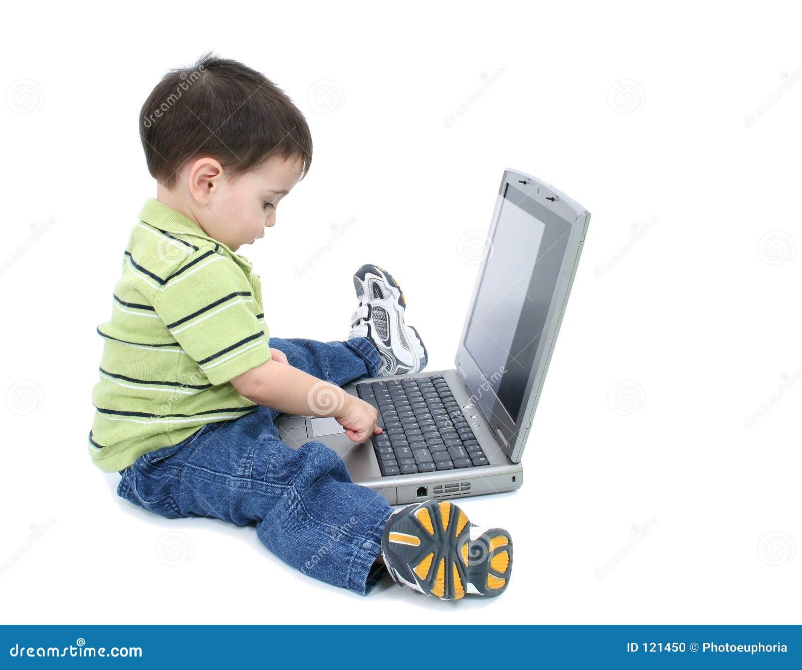 在空白工作的可爱的男孩膝上型计算&#