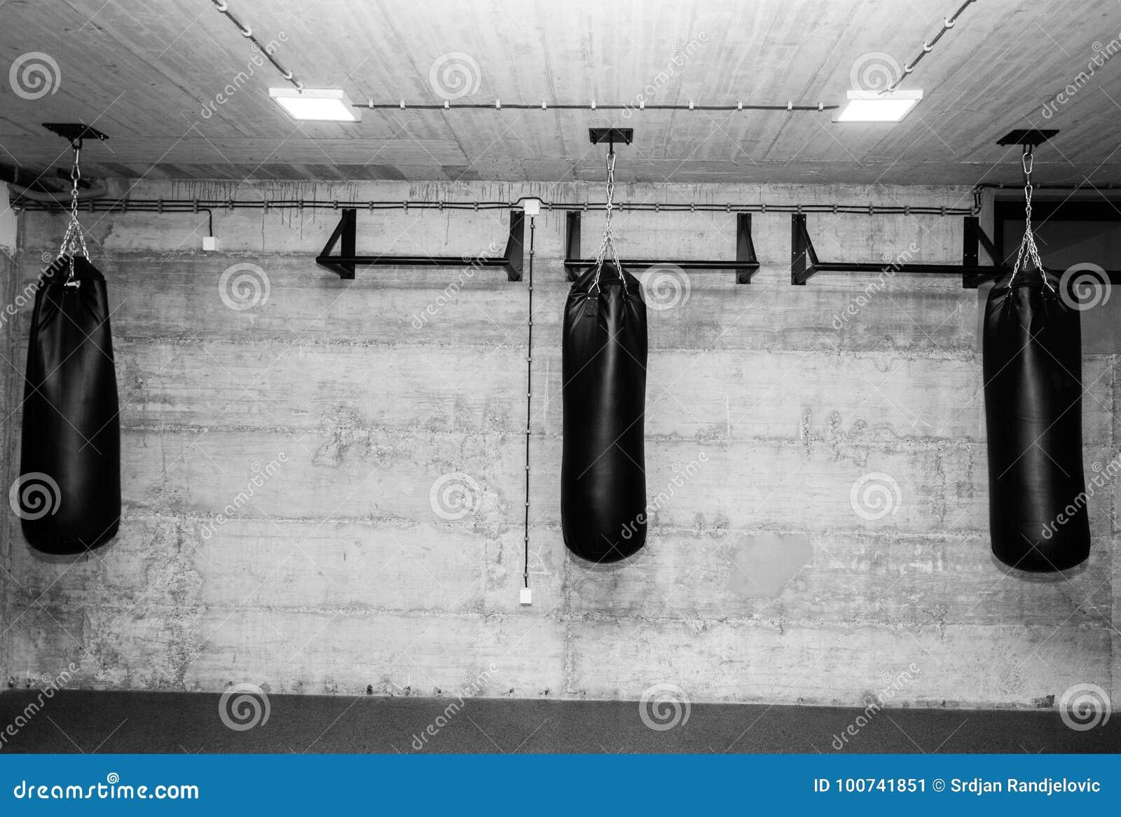 在空的拳击健身房的三个黑沙袋与赤裸难看的东西墙壁在黑白的背景中