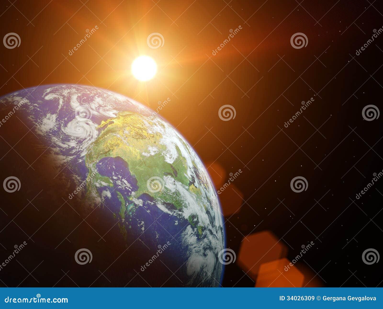 在空间的行星地球与发光在它后的太阳.