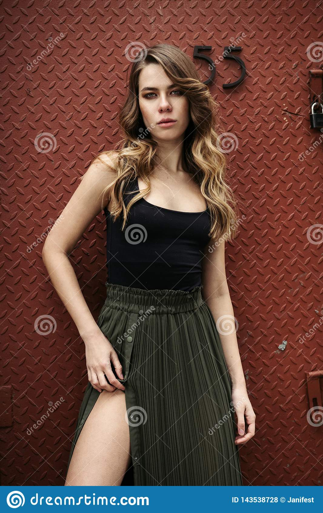 在穿着黑顶面和绿色长的性感的裙子的金属墙壁附近的时髦的时装模特儿女孩姿势