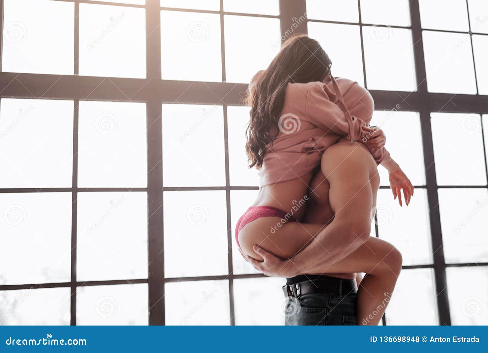 在窗口的热的年轻夫妇立场和掩藏头在毛线衣下 妇女坐人并且拥抱他与腿 人拿着她