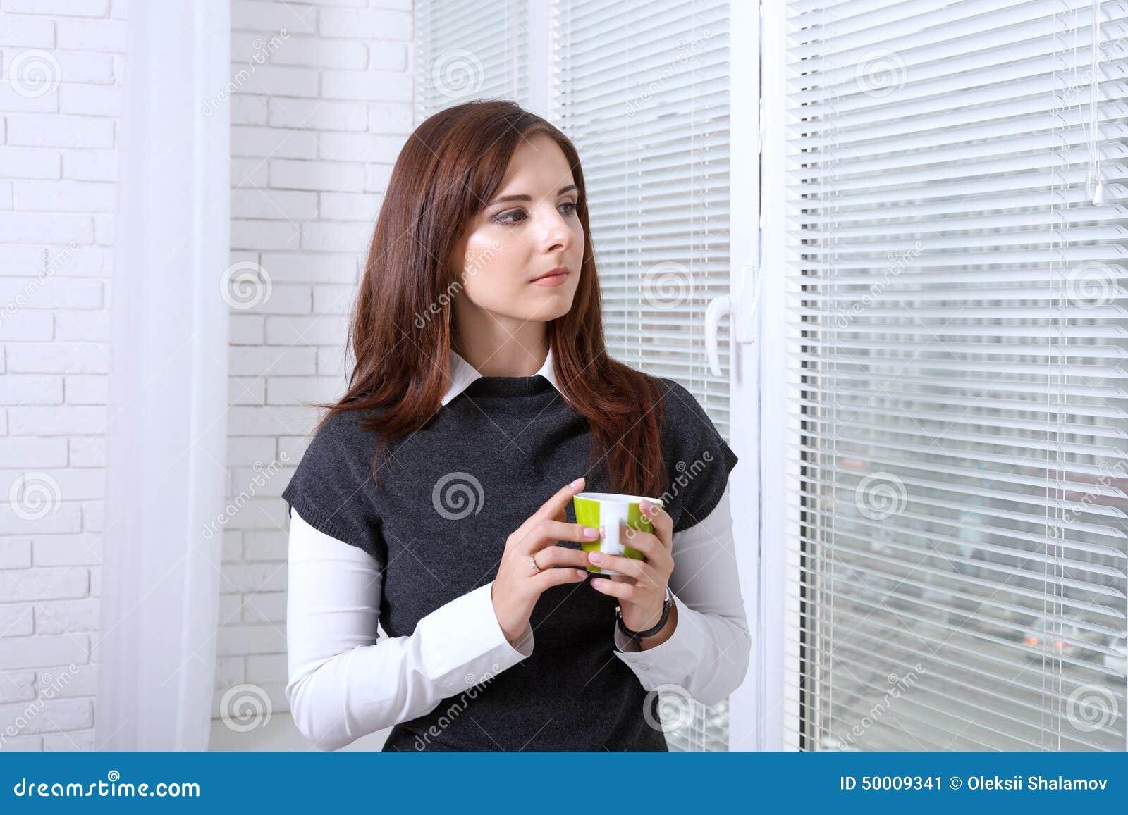 在窗口附近的妇女饮用的咖啡