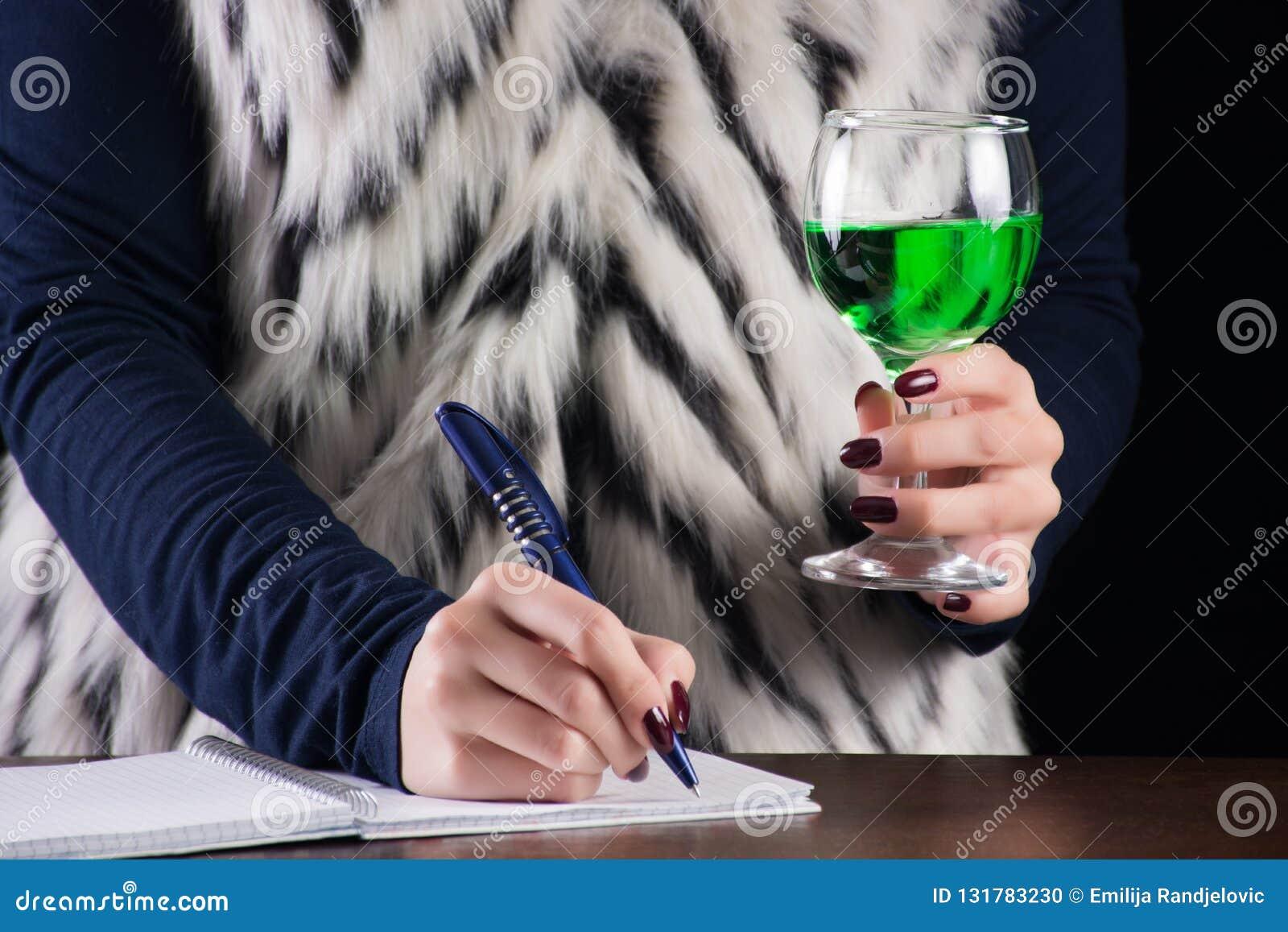 在笔记本和举行苦艾酒精饮料的女孩文字在手中